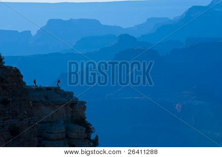 Tourist posing on cliff at Grand Canyon with blue background