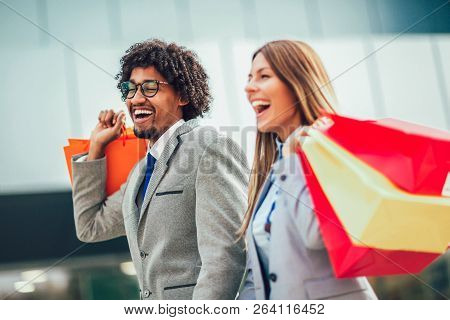 Couple In Shopping. Happy Couple With Shopping Bags Enjoying In Shopping.