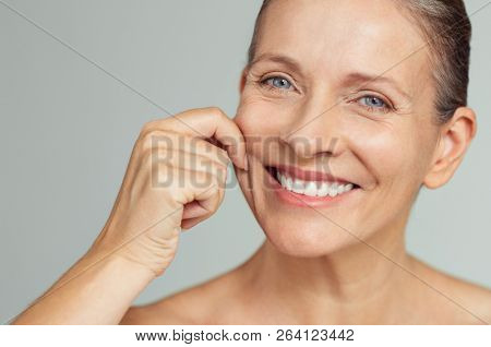 Senior woman pulling cheeks to feel softness and looking at camera. Beauty portrait of happy mature woman smiling with hands on cheek isolated over grey background. Aging process and skin concept.