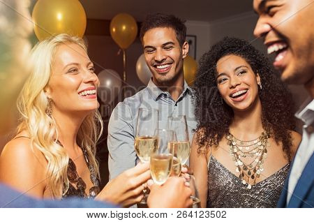 Group of five multiethnic friends enjoying at house party. Young men and beautiful women holding wine glasses raising toast. Cheerful smiling girls and guys celebrating at home with champagne.