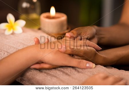 Closeup of woman getting manicure treatment in spa. Woman doing hand massage at wellness center. Detail of beautician hands doing massage hands to customer with candle on towel.