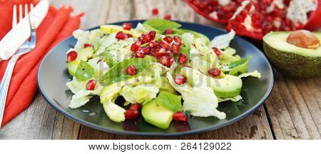Vegetarian Salad With Avocado, Greens, Leaves, Pomegranate And Letuce Leaves. Wooden Rustic Table.