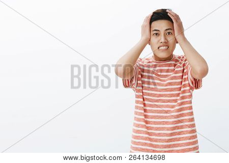 Guy pressing hands to head and clenching teeth being anxious and concerned having troubles forgetting to make important task in time, standing perplexed and upset with nervousness over white wall poster