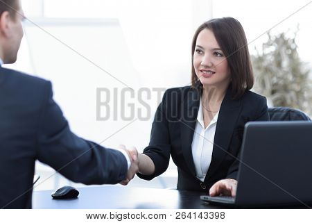 business woman shaking hands with a business partner over a Desk