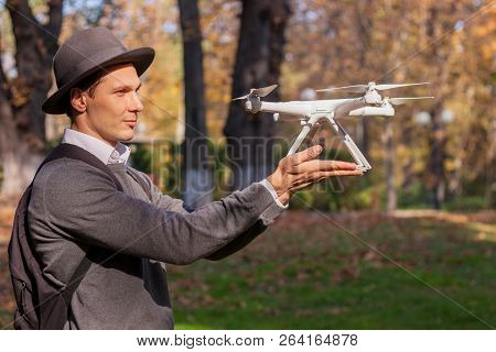 The UAV drone and photographer man hands close-up.drone copter flying with digital camera. Flying camera take a photo and video. poster