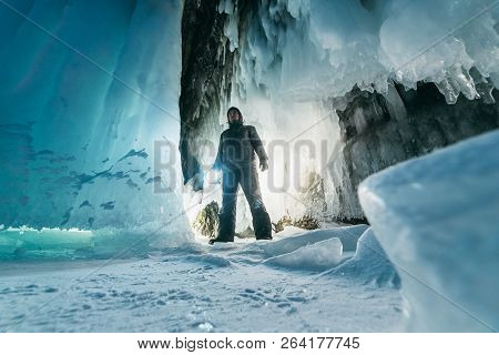 Surreal Landscape With Man Exploring Mysterious Ice Grotto Cave. Outdoor Adventure. Man Exploring Hu