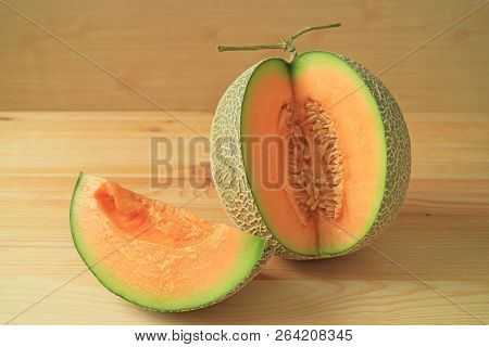 Juicy Fresh Ripe Muskmelon Sliced From The Whole Fruit Isolated On Wooden Background