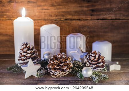 Festive Burning Advent And Christmas Candles With Traditional Decoration, First Advent