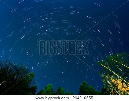 Moving Stars Drawing Light Trail On Dark Autumn Night Sky