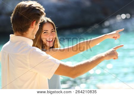 Happy Couple Of Teens Pointing Away On The Beach On Vacation In A Sunny Day