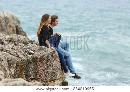Happy Teenage Couple Looking At Horizon On A Cliff With The Sea In The Background
