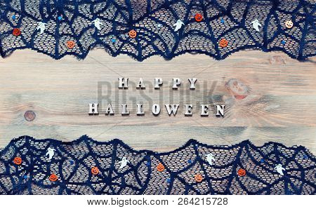 Halloween festive background. Happy Halloween wooden letters and Halloween decorations on the dark wooden background