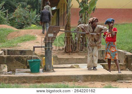 Abetifi, Ghana: July 27th 2016 - Two Boys Filling Bucket At Well In Rural Ghana.