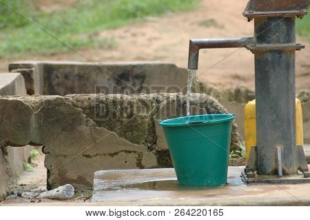 Green Plastic Bucket Being Filled With Water At Well In Ghana.