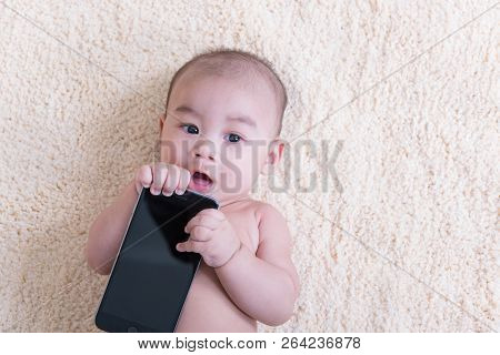 Asis Lying Baby Child Is With Mobile Phone Blank Screen.