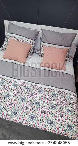 Comfortable Bed With Design Coverlet And Pink Pillows In Grey Bedroom Interior