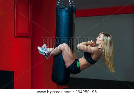 Young Beautiful Woman Doing Abs Workout Functional Crossfit Training On Punching Bag. Strong Muscula