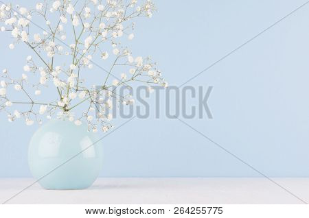 Spring Branch With Small White Flowers In Blue Sphere Vase In Soft Light Blue Modern Interior, On A