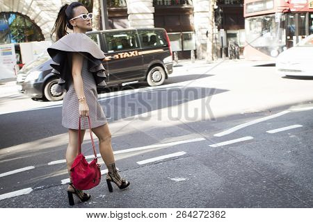 Asian Woman With A Ponytail In A Checkered Dress From Burberry And A Red Bag Walking Down The Street