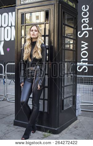 Skinny Blonde In Black Leather Trousers And Denim Jacket
