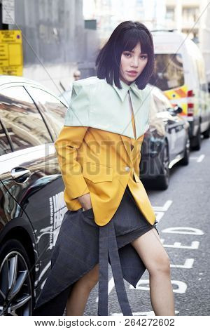 Chinese Blogger In A Yellow Jacket And Green Cape
