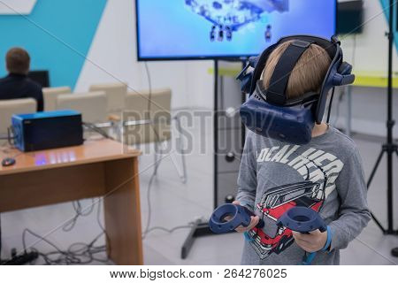 Little boy in vr headset playing virtual reality game with controllers on cybersport event poster