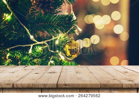 Empty Wood Table And Christmas Pine Cones Hanging From Christmas Tree With Display Montage For Produ