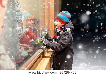 Cute Little School Kid Boy On Christmas Market. Funny Happy Child In Fashion Winter Clothes Making W