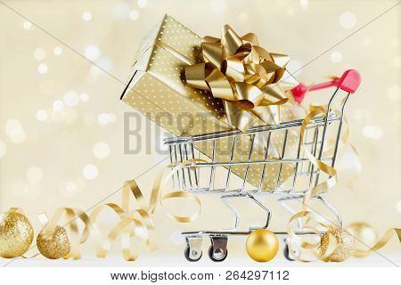 Shopping Cart With Gift Or Present Box On Golden Bokeh Background. Christmas And New Year Sale Conce