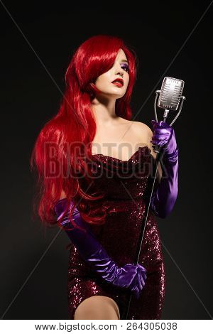Young Redhead Woman With Very Long Hair In Red Gown With Microphone On The Stand On A Black Backgrou