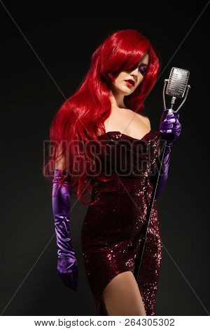 Young Luxury Redhead Woman With Very Long Hair In Red Gown With Microphone On The Stand On A Black B