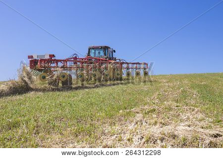 Tractor raking hay over sloped ground. Heavy wire spokes wheels made are pulled by a tractor for gather furrows of cut hay poster
