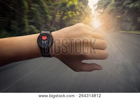 Runner Checking At Heart Rate Monitor Smart Watch Running On Road In Forest, Color Effect
