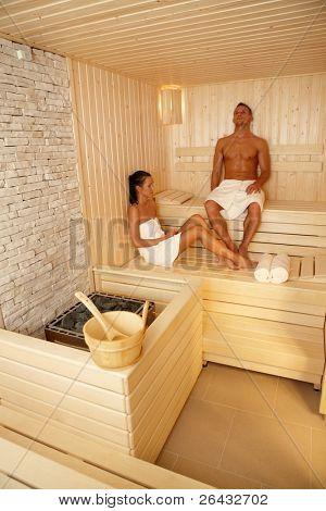 Couple relaxing in sauna on wellness trip, enjoying healthy program.?