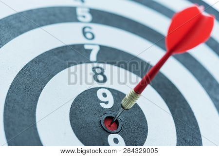 Red Dart Target Arrow Hitting On Bullseye, Metaphor To Target Marketing And Business Success Concept