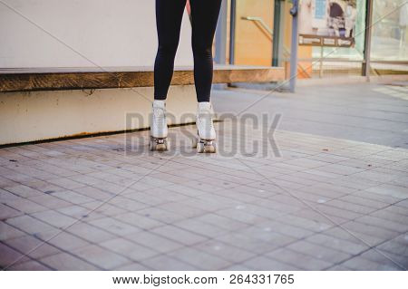 Image Of Woman Wearing Rollerskates Standing On Pavement