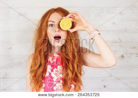 Excited Young Woman Holding Covering Eyes With Two Slices Of Lemons