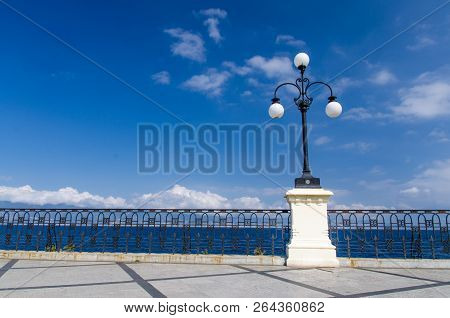 Street lamp lights with bolls on quay waterfront promenade Lungomare Falcomata in front of blue sky white clouds, Strait of Messina and Sicilia island background, Reggio di Calabria, Southern Italy poster