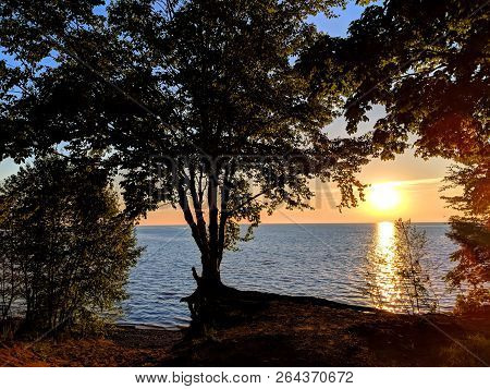 Beautiful Lake Superior Sunset Framed By Dense Forest Cover Of Northwoods Michigan