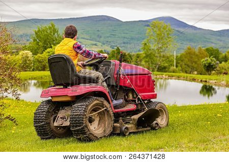 Landscaping Job For Teenager. Boy On A Riding Lawn Mower Cutting The Grass. Back View. Copy Space Fo