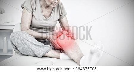 Senior woman with her hands on a painful knee against highlighted pain