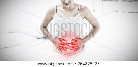 Casual woman with stomach pain sitting in bed against highlighted pain