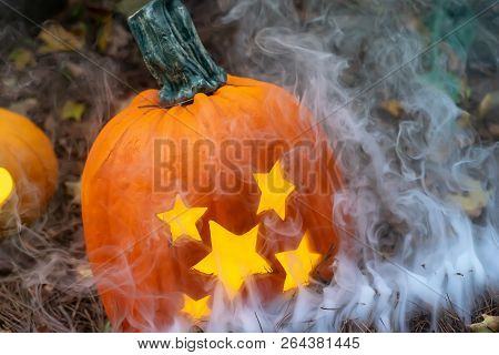 Jack O Lantern Sitting In Fall Leaves With White Smoke