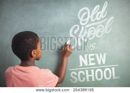 Old school vs new school against boy writing with chalk on greenboard in school