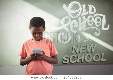 old school vs new school against boy using cellphone against greenboard in school