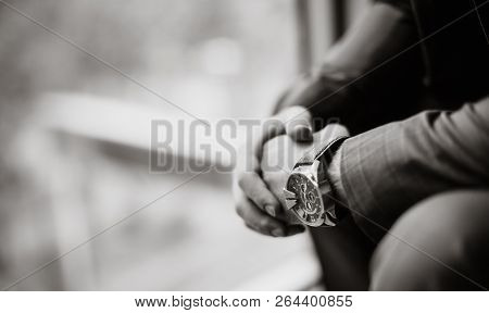 Black And White Photo Of A Businessman In A Suit With A Watch On His Hand. Blurred Background. Close