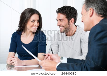 Financial consultant presents bank investments to a young couple poster