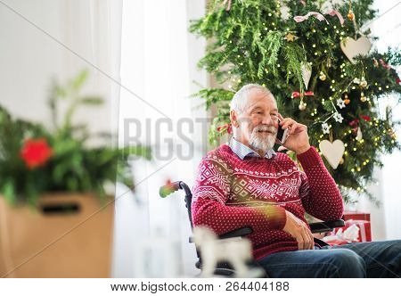 A Senior Man In Wheelchair With Mobile Phone At Home At Christmas Time, Making A Phone Call.