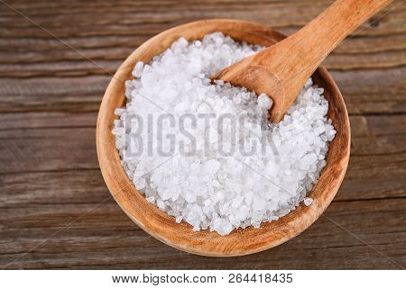 Crystals Of Large Sea Salt In A Wooden Bowl And Spoon On A Table. Background For Advertising Salt. T