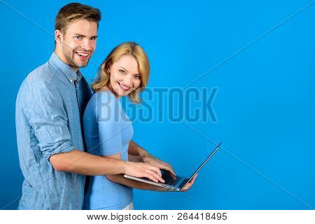 Happy Couple With Laptop. Stylish Guy Hugs Girl. Modern Technology, Internet And Communication. Coup
